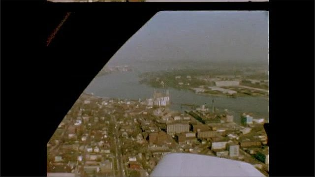 1940s: UNITED STATES: overhead view of flood water and river. Men talk by water. Man on barge.