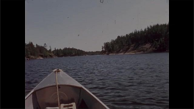 1940s: UNITED STATES: view along lake from canoe. Canoe on water. Trees on shore.