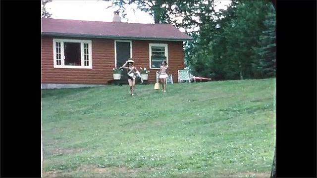 1960s: Woman and girl walk down grassy hill, away from cabin.