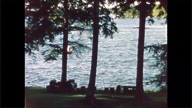 1960s: Lake, trees. People play tug of war.