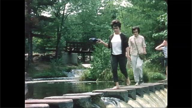 1960s: Women walk across stone on top of small waterfall.
