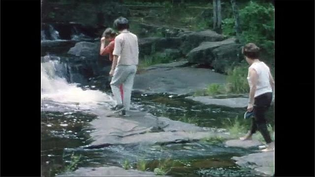 1960s: Women and girl hike across rocks near waterfall.