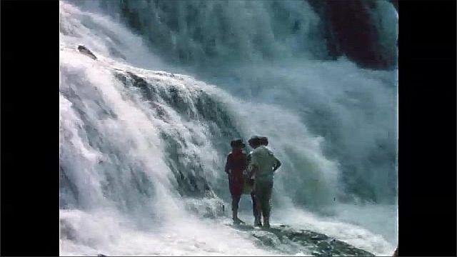 1960s: Women and girl stand on rock at base of waterfall.