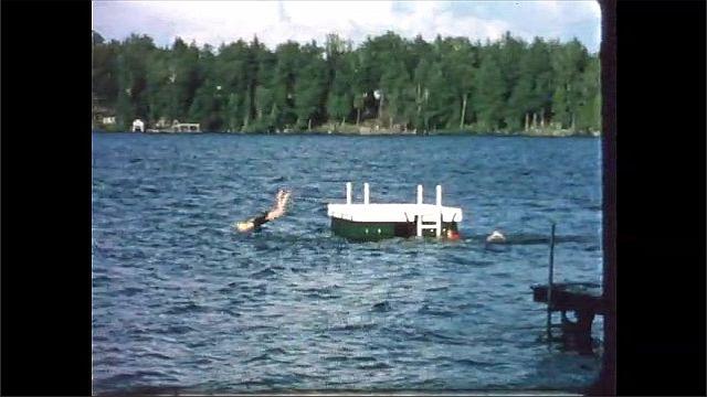 1960s: Women swim to platform in lake, dive off platform.