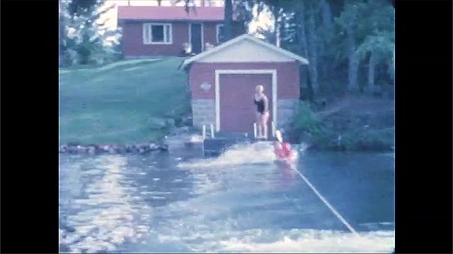 1960s: Person water skis behind boat. Person tries to waterski, falls, tries again, falls, tries again, stays up and then falls.