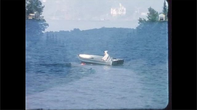 1960s: Person rows boat in water. Person swims in water. Road through forest.