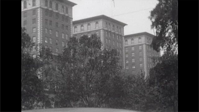 1920s: Tall buildings, trees, park. People walk around city, cars parked on street. People in park.