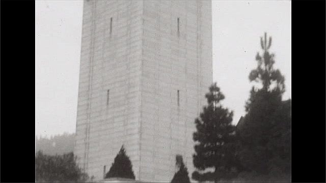 1920s: Cars parked on street, grass, trees, tall bell tower.