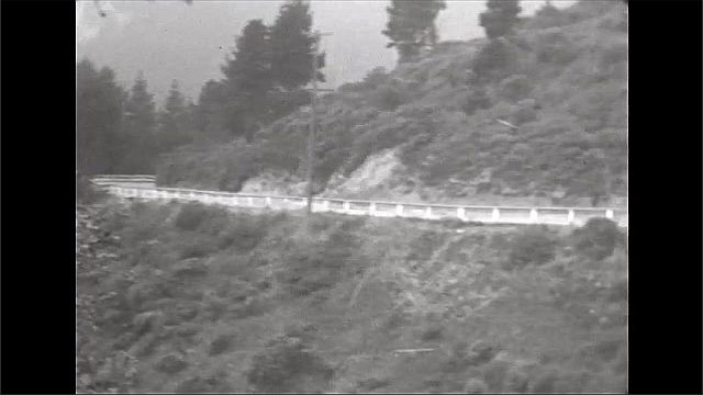 1920s: Mountain road. Car drives on road.