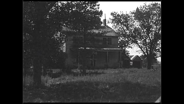 1920s: UNITED STATES: tree by swamp. House in grounds. Old house and grass.