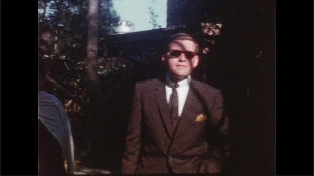 1950s: UNITED STATES: lady smiles at camera. Man in suit. Family wait outside house Man in sunglasses.