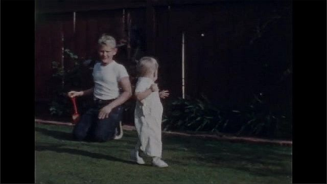 1940s: Older blonde boy kneels and pets a Collie dog as the blonde toddler approaches the dog. The toddler and the boy pet the Collie. Blonde toddler in brown overall toddles down sidewalk.