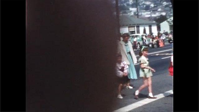 1940s: Children in halloween costumes parade down street.