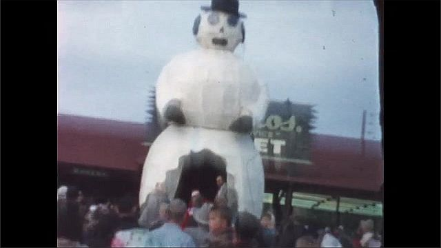 1940s: People stand around next to giant inflatable snowman.