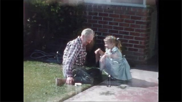 1940s: Girl stands on front steps of house. Man sits in grass in yard, talks to girl. Girl hugs and kisses man.