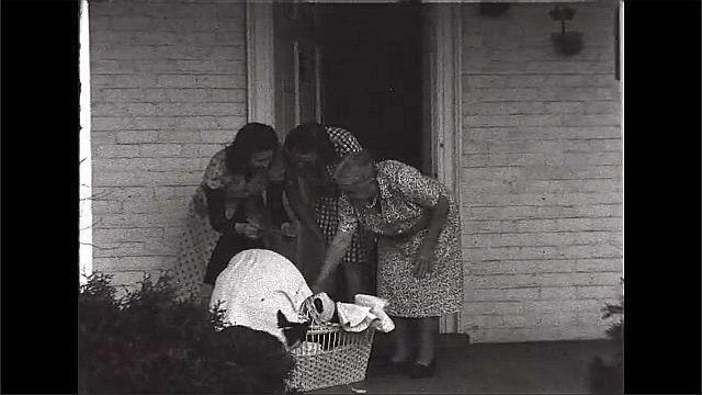 1940s: UNITED STATES: ladies come to doorstep. Baby in cot. Ladies look at baby on doorstep