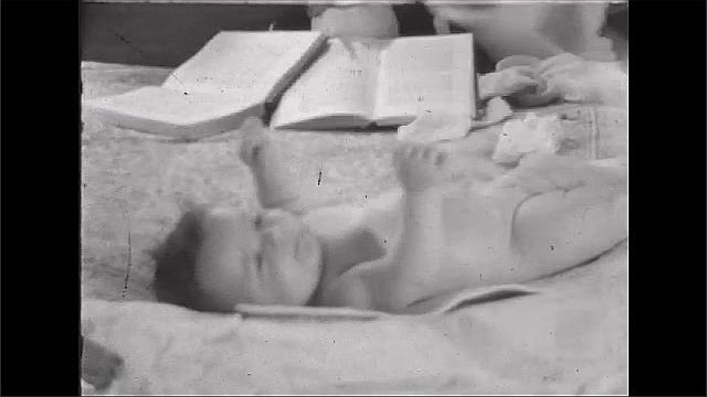 1940s: UNITED STATES: lady cleans and dries baby on changing mat. Lady fans baby. Hand flicks through book.