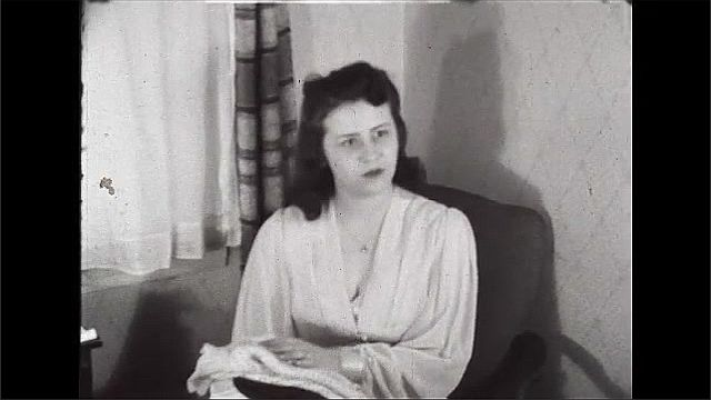 1940s: UNITED STATES: man talks to lady in room. Lady throws down magazine