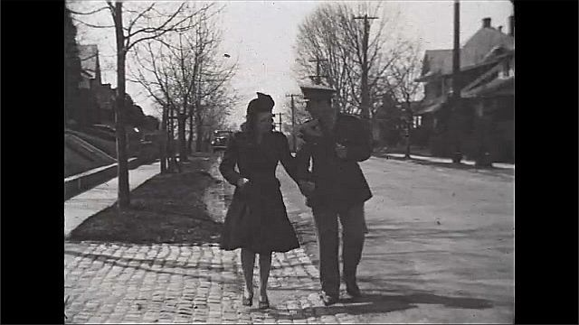 1940s: UNITED STATES: lady and man hold hands in street. Couple walk along street. Man in uniform