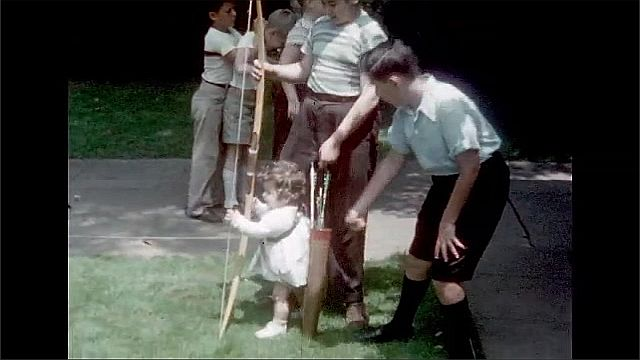 1930s: Boys play with boy and arrow with little girl.
