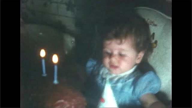 1930s: Woman touches child's hair. Lit candles on birthday cake. Candles are snuffled. Woman places party hat on child's head.