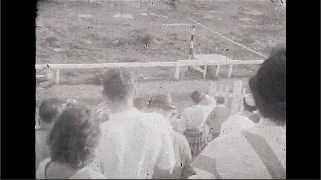 1930s: UNITED STATES: people in stalls at horse race. Riders and carts.