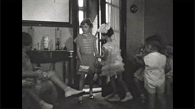 1930s: Kids in living room, girl runs to door, opens door, girl enters.