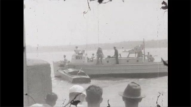 1930s: Two boats in water with people on board trying to tow third boat. Boat tows smaller boat into dock as people on shore watch.