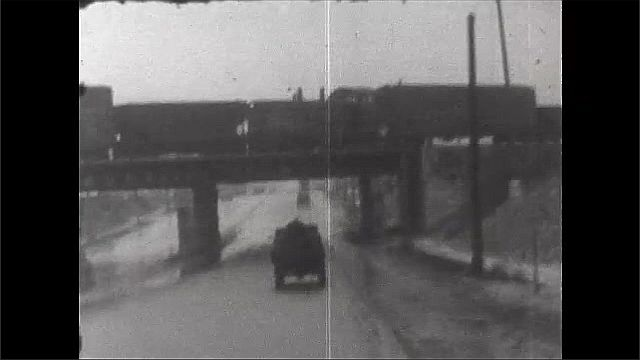 1930s: Driving down urban road, under train overpass and pass businesses.