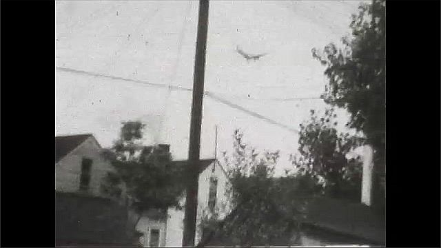1930s: View of tops of houses, phone pole. Shots of plane flying. Pan of plane flying overhead.