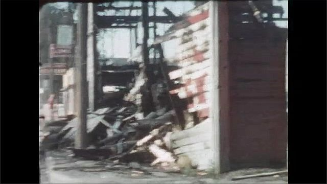 1950s: UNITED STATES: fence around crumbled building. Derelict building