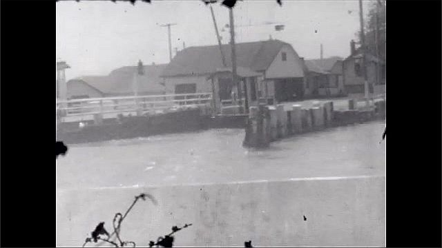 1930s: UNITED STATES: view of water and reeds from boat. Flooded area. Car drives through flood.