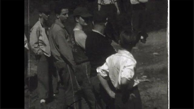 1930s: UNITED STATES: men watch game of horseshoes. Man with horseshoe.