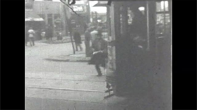 1930s: UNITED STATES: film in reverse. People in city street. Car on road. Tram on road