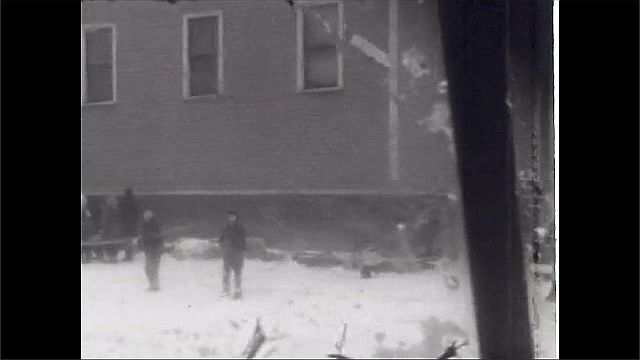 1930s: UNITED STATES: snow on ground in street. People walk in snow along sidewalk. Furniture store. Man in car.