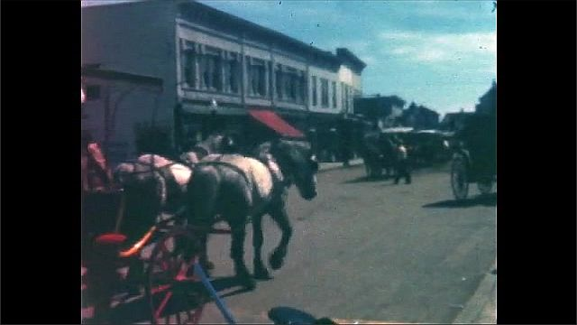 1940s: View of carriages on street, horses pull carriage past camera. View of ship next to pier.