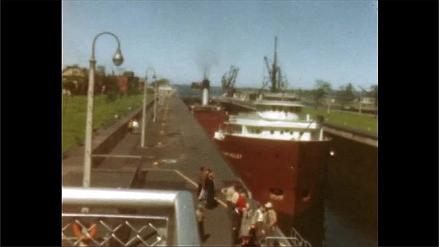 1940s: High angle view of ship in canal, people on pier.