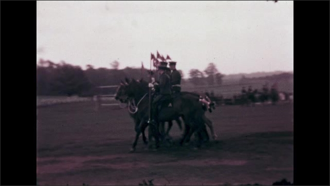 1940s: Men on horses with flags move in formation. Horses and riders perform stunt.