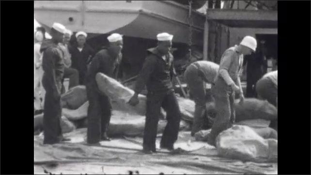 1920s: UNITED STATES: soldiers march up slope onto ship. Sailors carry supplies across deck. Train delivers supplies to ship.