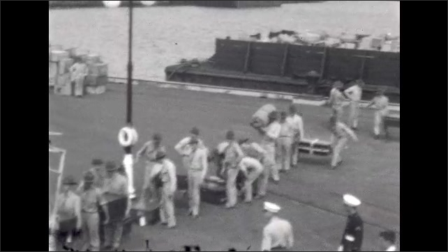 1920s: UNITED STATES: sailors carry supplies up gangplank onto ship. Soldiers carry supplies from train on dock to ship. View of dock from deck of ship