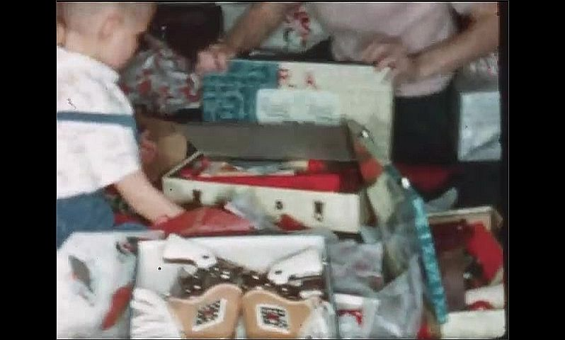 1940s: Woman and children sit on floor, open presents. Boys play with toys.