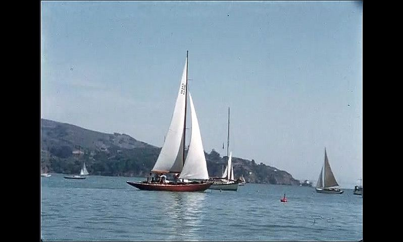 1950s: UNITED STATES: A Day on the Bay title. Yacht at sea. Waves on ocean. Boats sailing by coast. Boats sail around buoy.