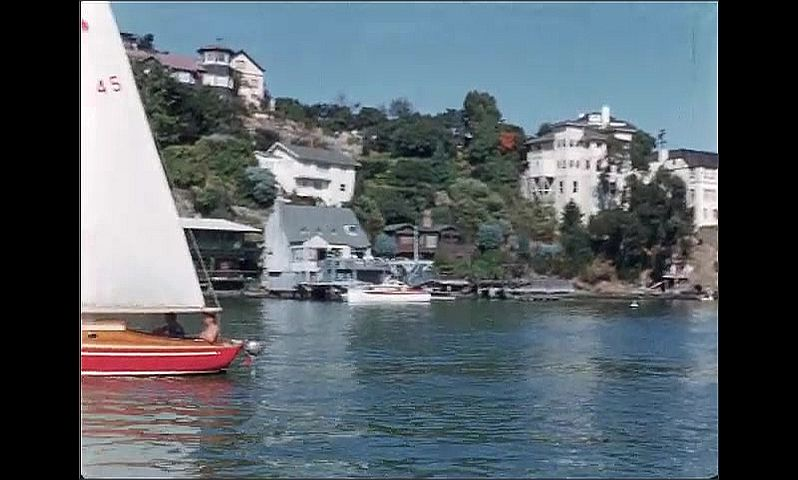 1950s: UNITED STATES: boat on mooring in bay. View of buildings from bay. Sailing boat on water in bay. Man on boat