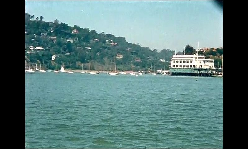 1950s: UNITED STATES: view across bay from water. Buildings and settlement on coastline.