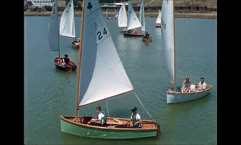 1950s: UNITED STATES: sailing boats in bay. Topper boats and young sailors. Lady on boat. Dinghy sailing in bay