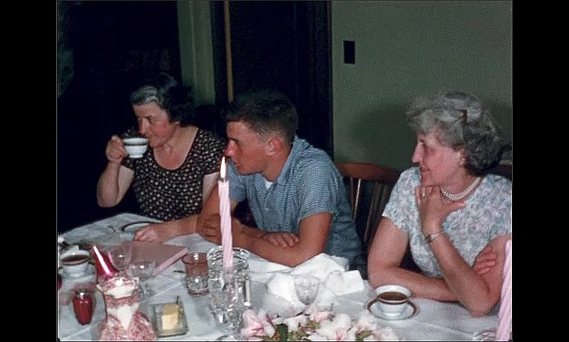 1950s: UNITED STATES: family sit at table together for coffee. Candles on table. Lady opens gifts.