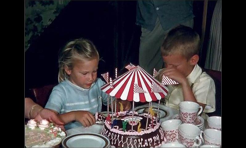1950s: UNITED STATES: lady cuts cake with girl. Lady serves cake onto plates. Girl eats cake.