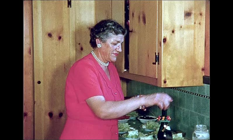 1950s: UNITED STATES: lady pours glass of wine from bottle. Girl and lady in kitchen. Ladies leave room