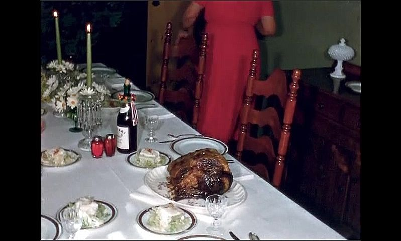 1950s: UNITED STATES: lady brings roast to table on plate. Roasted meat on table