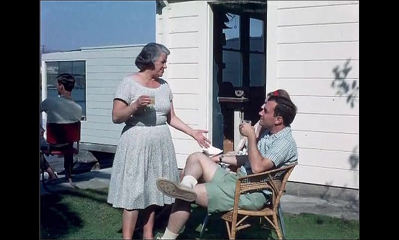 1950s: UNITED STATES: lady and man sit on porch. Lady on porch with glass.